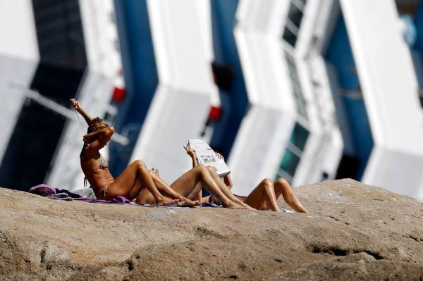 Women sunbathe in front of the wreckage of capsized cruise liner Costa Concordia near the harbour of Giglio Porto
