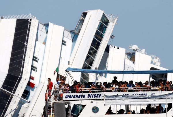Tourists on a ferry travel past the capsized cruise liner Costa Concordia, near the harbour of Giglio Porto
